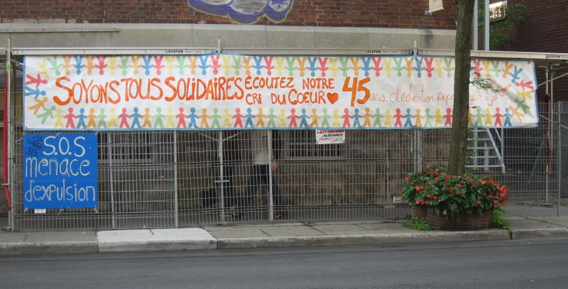 """Soyons tous solidaires!"" - Let's all stick together In acrylic paint on tyvek, participants worked together to design and paint this banner. Materials were donated by local businesses, with Harvey Lev of TechnoLith providing the tyvek, and Quincaillerie Lavoie and Rona donating paint. I sourced some materials, students others: often, the success of community practice can depend on the facilitator's ability to beg, borrow or salvage materials."