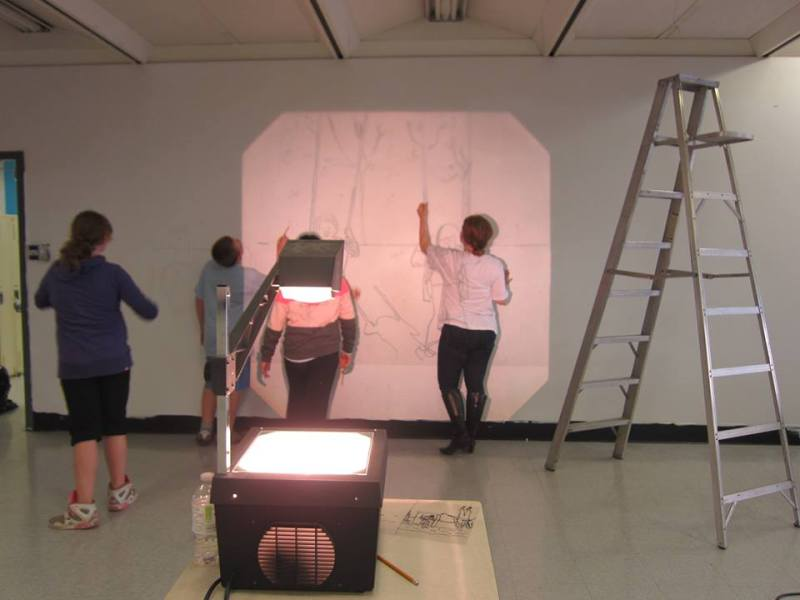 Transferring the preliminary design to the wall with the help of an overhead projector.